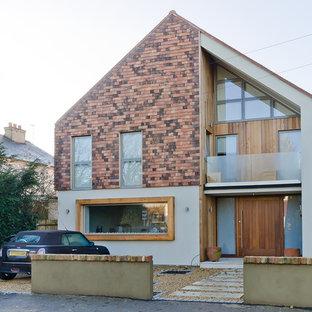 Idee per la facciata di una casa scandinava a tre o più piani con tetto a capanna e rivestimenti misti