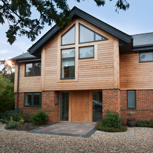 Brown rustic two floor detached house in Berkshire with wood cladding and a pitched roof.