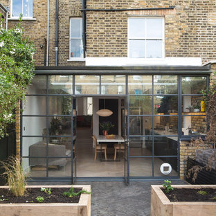 Inspiration for a large contemporary brick terraced house in London with a flat roof and a mixed material roof.