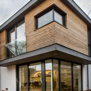 This is an example of a white contemporary two floor exterior in Oxfordshire with wood cladding.