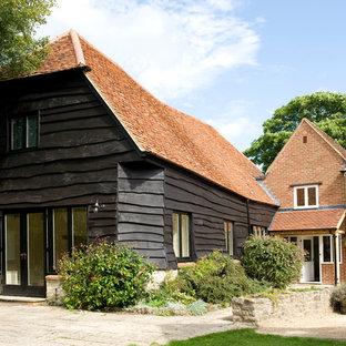 Foto della facciata di una casa grande country a tre piani con rivestimenti misti e falda a timpano