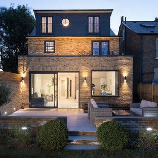 Large transitional beige split-level brick exterior home photo in London