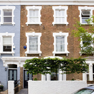 This is an example of a brown traditional brick terraced house in London with three floors and a flat roof.