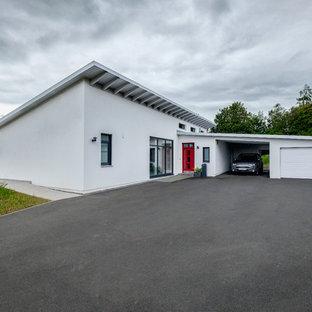 Свежая идея для дизайна: одноэтажный фасад частного дома белого цвета в стиле ретро с облицовкой из цементной штукатурки, односкатной крышей и металлической крышей - отличное фото интерьера