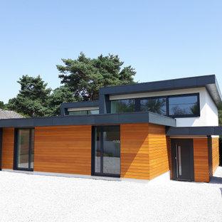 Bild på ett funkis flerfärgat hus, med två våningar, blandad fasad och platt tak