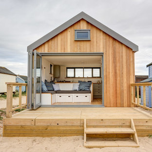 Photo of a small beach style one floor house exterior in Dorset with wood cladding and a pitched roof.