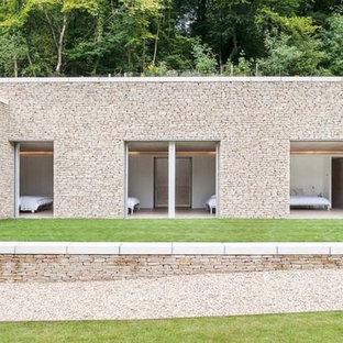 Ispirazione per la facciata di una casa beige moderna con rivestimento in pietra