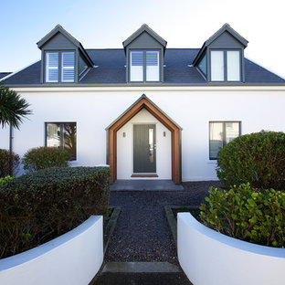 Inspiration for a white contemporary two floor detached house in Channel Islands with a pitched roof and a shingle roof.