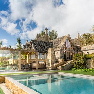 На фото: трехэтажный, бежевый частный загородный дом в стиле кантри с облицовкой из камня, двускатной крышей и черепичной крышей
