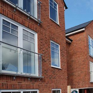 Diseño de fachada de piso roja, urbana, de tres plantas, con revestimiento de ladrillo, tejado a dos aguas y tejado de teja de barro