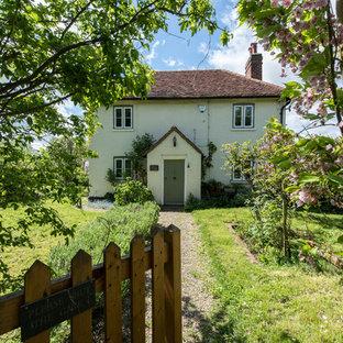 Immagine della facciata di una casa beige shabby-chic style a due piani con tetto a padiglione e rivestimento in mattoni
