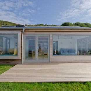 Photo of a small and beige contemporary one floor detached house in Cornwall with wood cladding and a flat roof.