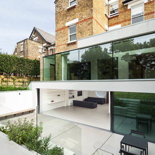 White and large contemporary glass exterior in London with a flat roof and three or more floors.