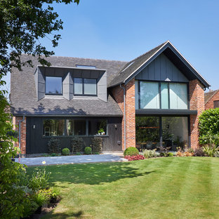 Large and red contemporary two floor brick detached house in West Midlands with a hip roof.