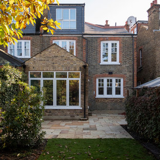 Example of a mid-sized classic two-story brick duplex exterior design in London with a hip roof and a shingle roof
