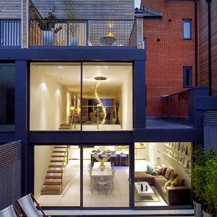 Immagine della facciata di una casa a schiera moderna a tre o più piani con rivestimento in vetro