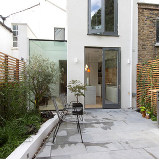 Design ideas for a mid-sized contemporary two-storey stucco white townhouse exterior in London.