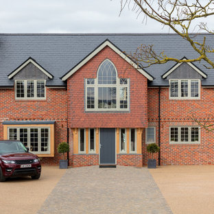 Photo of a large and red traditional brick detached house in Other with three or more floors and a hip roof.