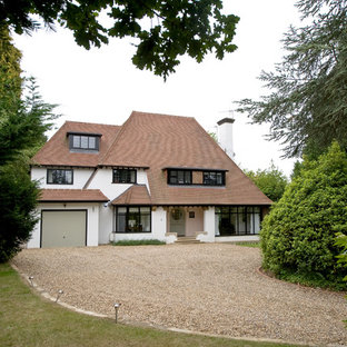Inspiration for a large and white classic render detached house in Surrey with three floors, a hip roof and a shingle roof.
