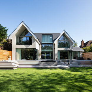 Photo of a white contemporary two floor detached house in Surrey with a pitched roof and a grey roof.