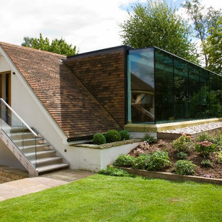 Immagine della facciata di una casa grande bianca contemporanea a due piani con rivestimento in vetro