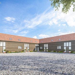 Ejemplo de fachada de casa pareada marrón, rural, grande, de dos plantas, con revestimiento de madera, tejado a la holandesa y tejado de teja de barro