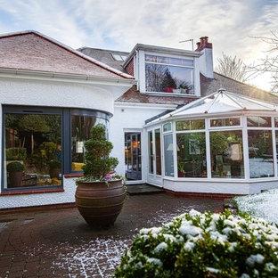 Modelo de fachada de casa blanca, minimalista, pequeña, con revestimiento de estuco, tejado a cuatro aguas y tejado de teja de barro