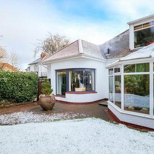 Foto de fachada de casa blanca, moderna, pequeña, con revestimiento de estuco, tejado a cuatro aguas y tejado de teja de barro