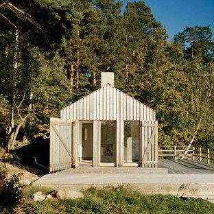 Inredning av ett minimalistiskt litet beige trähus, med allt i ett plan och sadeltak