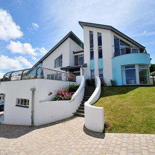 Immagine della facciata di una casa grande bianca stile marinaro a tre piani con rivestimenti misti e tetto a una falda