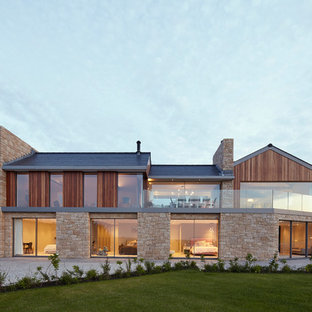 Inspiration for a beige contemporary two floor detached house in Channel Islands with mixed cladding and a pitched roof.