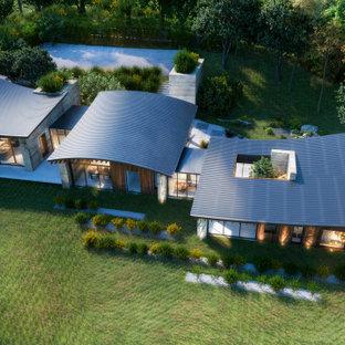 Réalisation d'une très grand façade de maison marron design à niveaux décalés avec un toit papillon et un toit en métal.