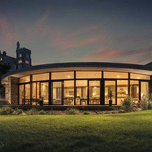 Foto della facciata di una casa unifamiliare contemporanea a un piano con rivestimento in vetro