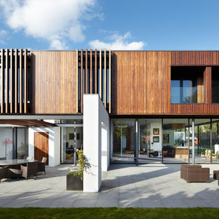 This is an example of a medium sized contemporary two floor detached house in Cheshire with wood cladding and a flat roof.