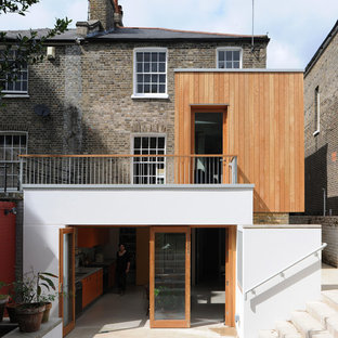 Photo of a medium sized contemporary terraced house in London with wood cladding, three floors and a hip roof.