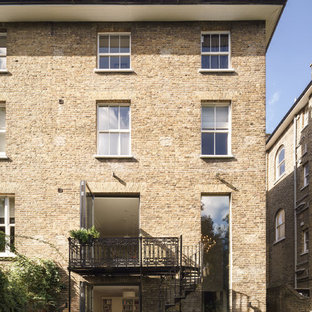 Design ideas for a beige classic brick exterior in London with three or more floors and a flat roof.