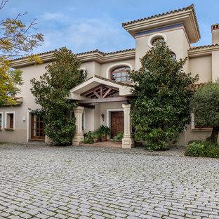 Ejemplo de fachada beige, tradicional, grande, de dos plantas, con revestimientos combinados y tejado a cuatro aguas