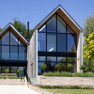 Large contemporary two floor detached house in Hampshire with wood cladding, a pitched roof and a metal roof.