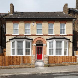 Cette image montre une grand façade de maison beige traditionnelle à trois étages et plus avec un toit à deux pans et un toit en tuile.
