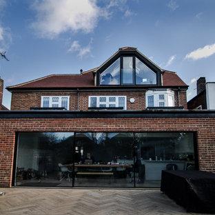 Mittelgroßes, Dreistöckiges, Orangenes Modernes Einfamilienhaus mit Lehmfassade, Walmdach und Ziegeldach in Surrey
