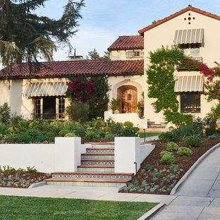 Foto de fachada de casa beige, mediterránea, grande, de dos plantas, con revestimiento de adobe, tejado a dos aguas y tejado de teja de barro