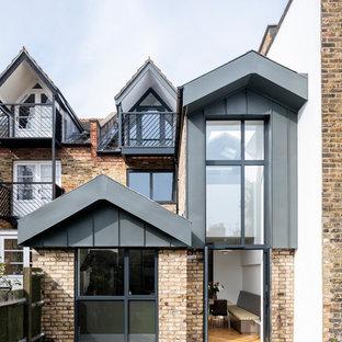 Imagen de fachada de casa multicolor, nórdica, grande, de dos plantas, con revestimientos combinados y tejado a dos aguas