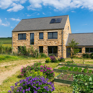 Photo of a rural two floor exterior in Other with stone cladding and a pitched roof.