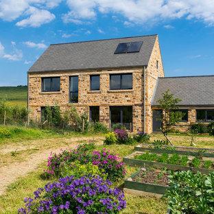 На фото: двухэтажные дома в стиле кантри с облицовкой из камня и двускатной крышей