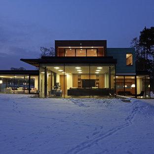 Imagen de fachada minimalista, de dos plantas, con revestimiento de vidrio y tejado plano