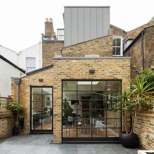 Foto de fachada de casa pareada marrón, ecléctica, de tres plantas, con revestimiento de metal, tejado a dos aguas y tejado de varios materiales