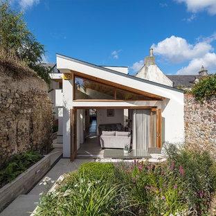 Inspiration för små moderna vita hus, med allt i ett plan, platt tak och stuckatur