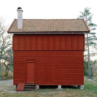 На фото: маленький, двухэтажный фасад дома красного цвета в скандинавском стиле с облицовкой из дерева и двускатной крышей с
