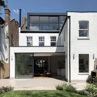Photo of a large contemporary brick white duplex exterior in London with three or more storeys.