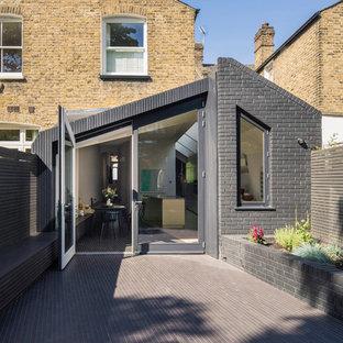 Idées déco pour une façade de maison noire contemporaine de plain-pied avec un toit à deux pans et un toit mixte.